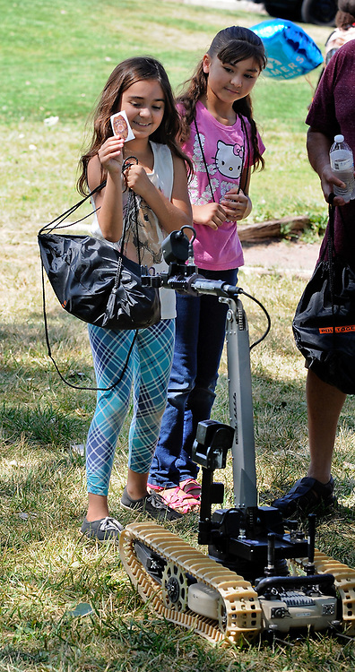 jt071417h/ a sec/jim thompson/left to right- Madalyn Brazil-9 gets a sticker delivered to her by a NM State Police bomb squad robot as her sister Jessalyn -10 looks on at Rotary Park in Bernalillo,NM  as they attend the Cops in the Park celebration. Friday,  July. 14, 2017. (Jim Thompson/Albuquerque Journal)