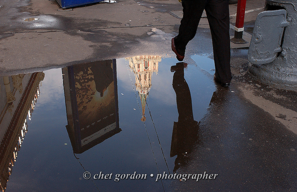 A pedestrian walks past a puddle in central Moscow, Russian Federation on June 22, 2005.
