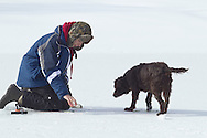 Middletown, New York - A boy ice fishes as a dog looks on at the Shawangunk Fish and Game Association pond during the association's annual contest on Feb. 8, 2014. ©Tom Bushey / The Image Works