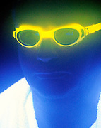 Portrait of a man with glowing goggles in a fog.Black light
