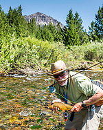 A Wyoming high mountain stream fishermen showing off his worthy catch. The size of the wild trout of the Greater Yellowstone region is amazing.