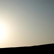 Oman, Wahiba Sands. January/26/2008...A lone figure takes in a desert sunrise.