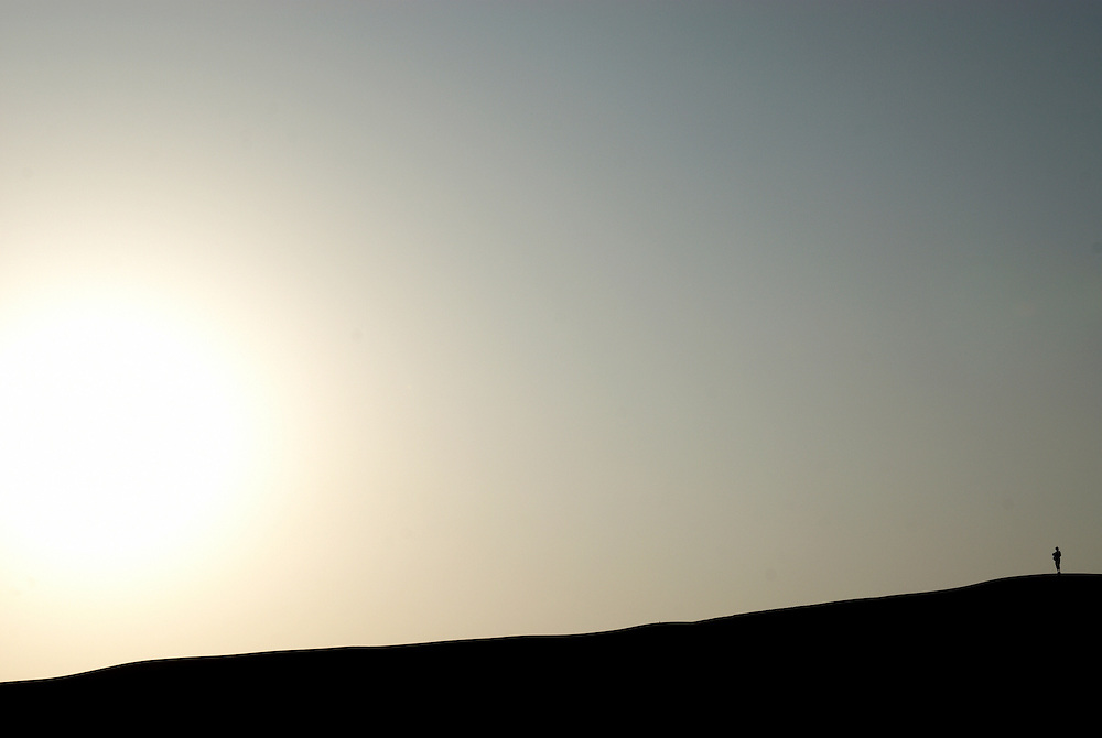 Oman, Wahiba Sands. January/26/2008...A lone figure takes in a desert sunrise.