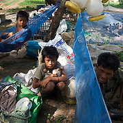 An eleven-year old boy (center) rests at a duck farm where he works after his mother pulled him out of school in Siem Reap, Cambodia and sent him to the farm  in a village at the base of Phnom Krom because he was not performing in class and the family needed the extra income.  Two sons (left) of the duck farmer (center) rest with him; they have never attended school.