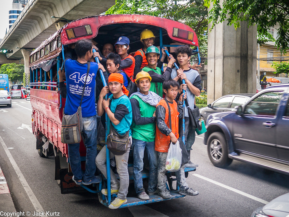 """07 OCTOBER 2012 - BANGKOK, THAILAND: Construction workers crowd into the back of a """"songthaew"""" as they leave a job site at an international hotel on Sukhumvit Road in Bangkok. A songthaew is a pickup truck converted to a bus or shared taxi by the installation of two bench seats in the back. They are commonly used in rural areas and as company provided transport in Malaysia, Thailand and Laos.     PHOTO BY JACK KURTZ"""