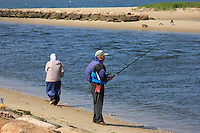 In the early cool morning a retired couple husband and wife fish  on the beach in Cape Cod Massachusetts.