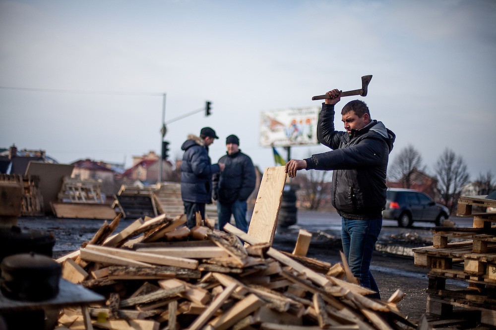 """Activist """"Bosch"""" preparing fire wood with an axe at the barricades blocking a building supplies store named """"Epicenter"""" in the city of Lviv, Ukraine."""