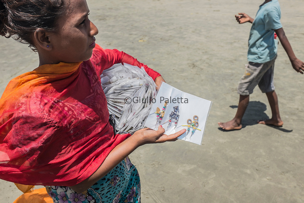 Asha, 10 years old, one of the surfer girls, selling hand-made jewellery that she made at home. Most of the surfer girls of her age, while not surfing, try to sell things on the beach of Cox's Bazar, Bangladesh