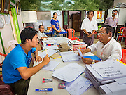 02 NOVEMBER 2015 - YANGON, MYANMAR: An elections worker (left) talks to a NLD campaign outreach worker (right) in an elections office in North Okkalapa township of Yangon. The NLD official visited the elections office with questions about voter rolls. Voter registration rolls were released Monday. Voters and party officials are double checking rolls to ensure accuracy. National elections are scheduled for Sunday Nov. 8. The two principal parties are the National League for Democracy (NLD), the party of democracy icon and Nobel Peace Prize winner Aung San Suu Kyi, and the ruling Union Solidarity and Development Party (USDP), led by incumbent President Thein Sein. There are more than 30 parties campaigning for national and local offices.    PHOTO BY JACK KURTZ