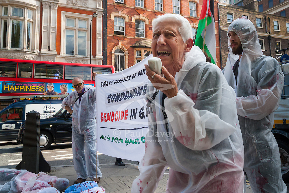 """London, August 4th 2014. A woman from British Jews Against Genocide protests against the Board of Deputies of British Jews' ongoing support for Israel's """"genocide"""" in Gaza as the Israeli attacks continue."""