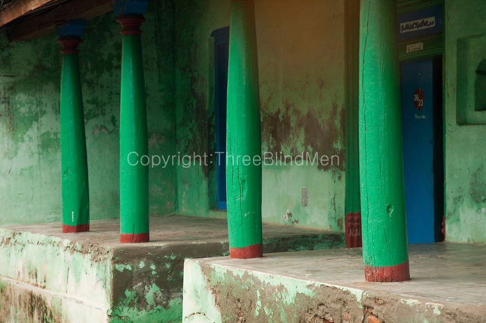 Exterior of a home in Nagapattinam with fine green pillars.<br />