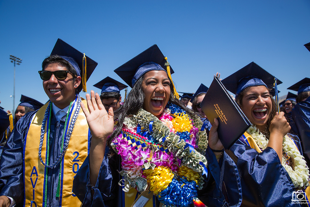 Marhiel Antoinette Laya (center) moves the tassel on her cap with classmates during the graduation ceremony at Milpitas High School in Milpitas, California, on June 6, 2015. (Stan Olszewski/SOSKIphoto)