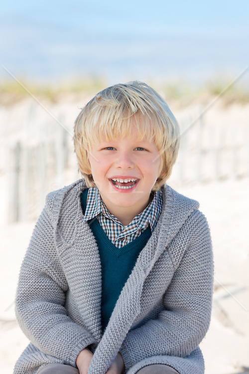 little boy on the beach in a sweater laughing