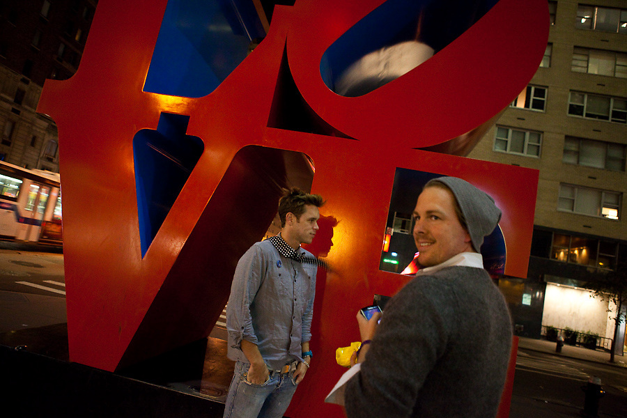 Two young men in front of the LOVE sculpture in New York City at night.