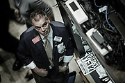 "Trading on NYSE the day after Congress agreed on a compromise enabling a 700 billion bail-out package. Floor Specialist Albert Young watching the stock ticker (in front of photographer). Next to him is the newest edition of BusinessWeek, with the frontpage reading ""Is it safe yet?"". Photo: Orjan F: Ellingvag/ Dagens Naringsliv"