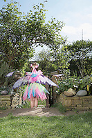 Young girl (5-6) wearing fairy costume standing in garden back view