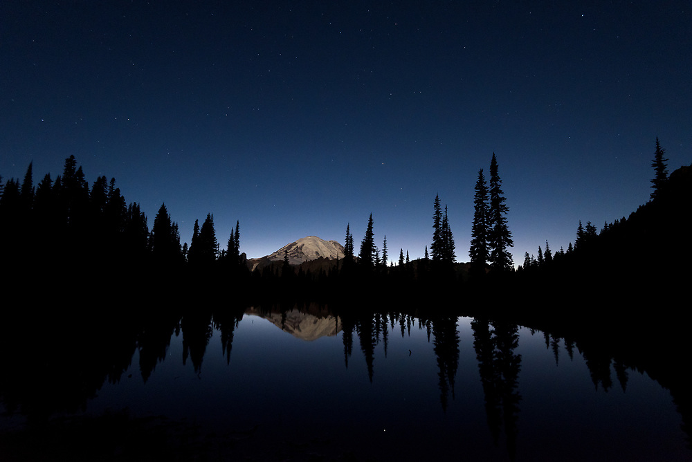 Mt. Rainier reflected in a small tarn, beneath the stars.