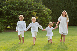 four kids dressed up and walking together on a lawn