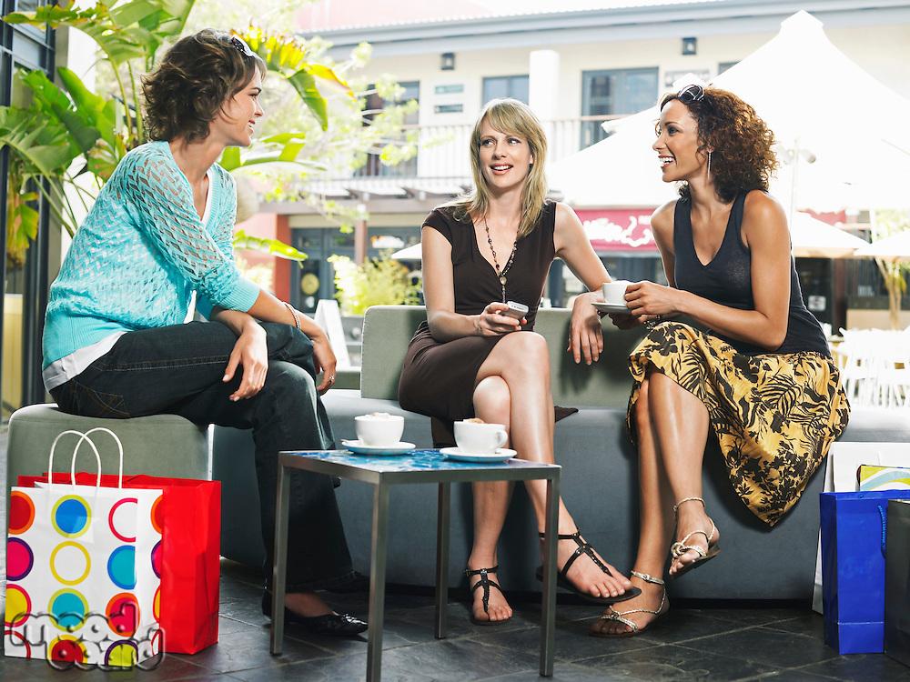 Three female friends talking in cafe