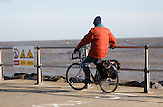 Man on bicycle looking out to sea, Ness Point, Lowestoft, Suffolk, England