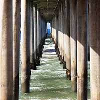 Under the pier in Orange County California with pier support columns. Huntington Beach Pier is located in Southern California along the Paicific Ocean.