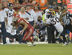 Sep 17, 2015; Kansas City, MO, USA; Kansas City Chiefs tight end Travis Kelce (87) runs the ball as Denver Broncos strong safety David Bruton (30) attempts the tackle during the second half at Arrowhead Stadium. The Broncos won 31-24. Mandatory Credit: Denny Medley-USA TODAY Sports