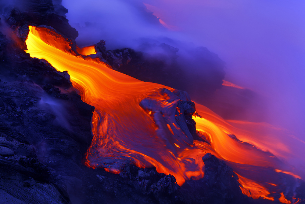 Lava pours out of a tube at the ocean's edge, creating a surreal, colorful and steamy scene, as the dynamic Kalapana coastline is altered forever.