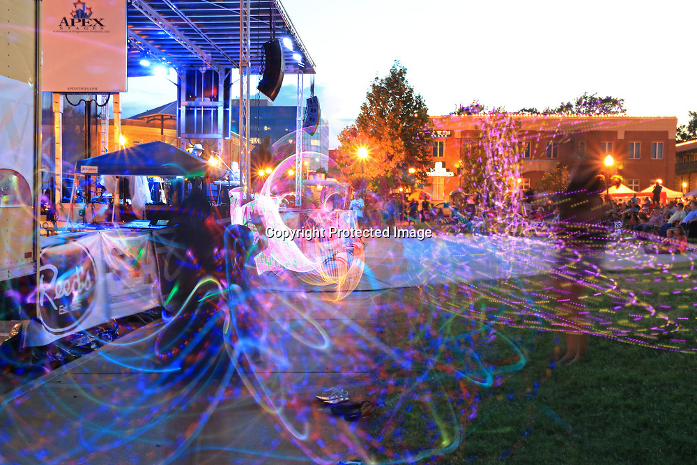 "(long exposure)-Ladies from the local club ""Hoop-elo"", turn their hula-hoops into dazzling ligh shows during Tupelo's Down on Main concert Thursday evening."