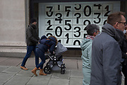Shoppers walk past a window display that features numbers - part of a design theme called 'State of the Arts', at the Selfridges department store on Oxford Street, on 4th March 2019, in London England. Darren Almond's piece &lsquo;Chance Encounter 004&rsquo;, consists of a grid formed from rectangular panels, featuring fragmented numbers that appear to scroll across the surface. <br /> State of the Arts is a gallery of works by nine crtically-acclaimed artists in Selfridges windows to celebrate the power of public art. Each of the artists are involved in creating a site-specific artwork at one of the new Elizabeth line stations as part of the Crossrail Art Programme.