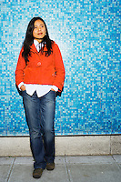 An early 30's / late 20's Asian woman (Japanese/Filipino) standing in front of a torquoise wall looking thoughtful..Model Release: 20070513_MR_A