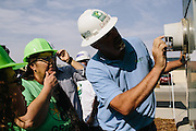 Madera California resident Maria Zavala, second from left, listens as David Griffin, a solar install supervisor with Grid Alternatives, gives her instructions on how to turn her solar panels on and off and how to read her meter after her home was retrofitted with solar panels from Grid.