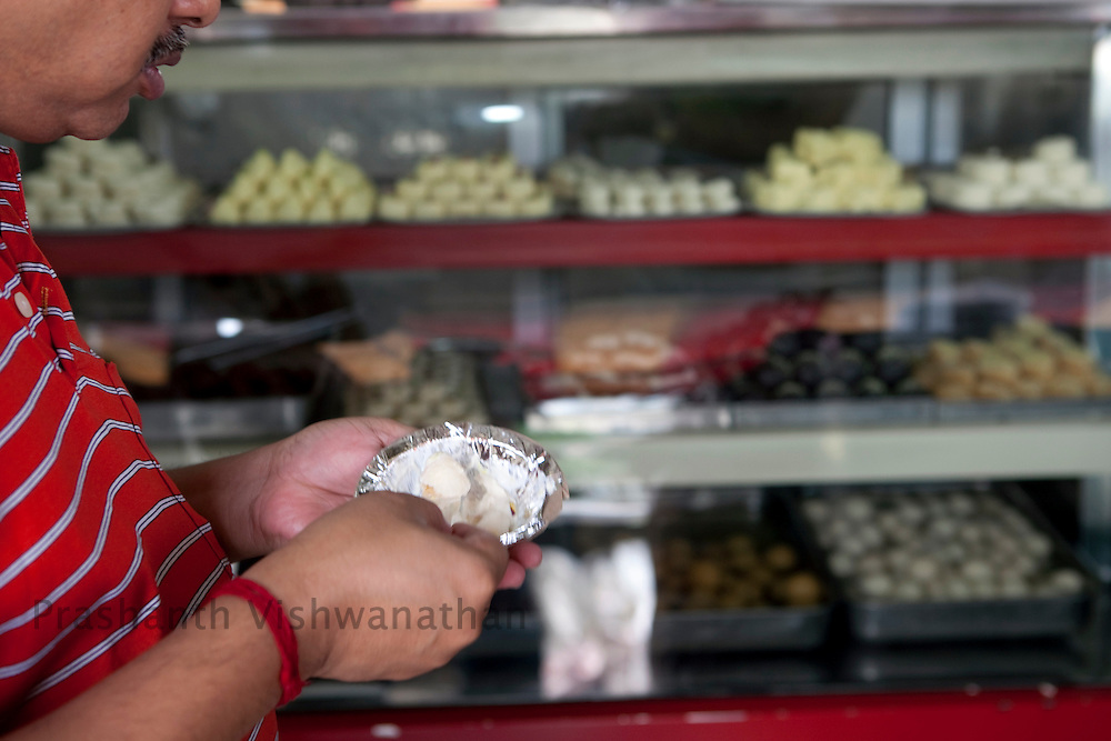 Customers buy sweets at a  sweet shop, in New Delhi, India, on Wednesday September 2, 2010. Photographer: Prashanth Vishwanathan/Bloomberg News