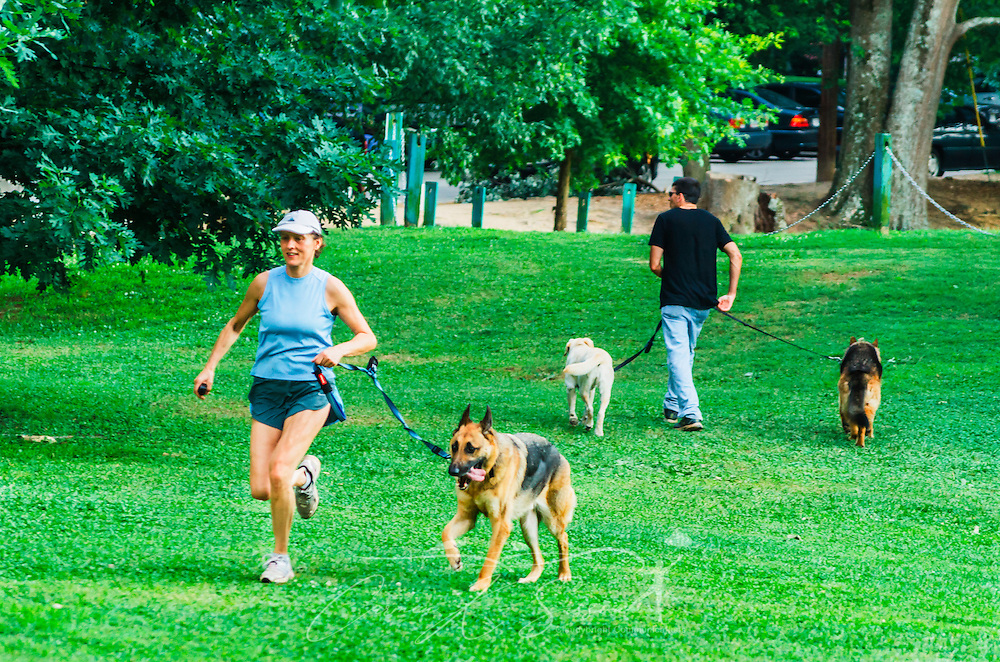 Pet owners walk their dogs at Candler Park, June 4, 2014, in Atlanta, Georgia. The 55-acre park features a golf course, swimming pool, football/soccer field, basketball court, tennis court, and playground. It was named after Asa Griggs Candler, who donated the property in 1922. (Photo by Carmen K. Sisson/Cloudybright)