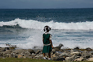 A schoolgirl looking at the sea at Pigeon Point, St Lucia, The Windward Islands,<br /> The Caribbean