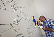 Jose Solano woeks on a mural in preparation for the first day of school at Mading Elementary School, August 20, 2014.
