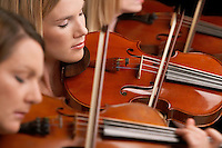 Women Playing Violins in musical group close-up