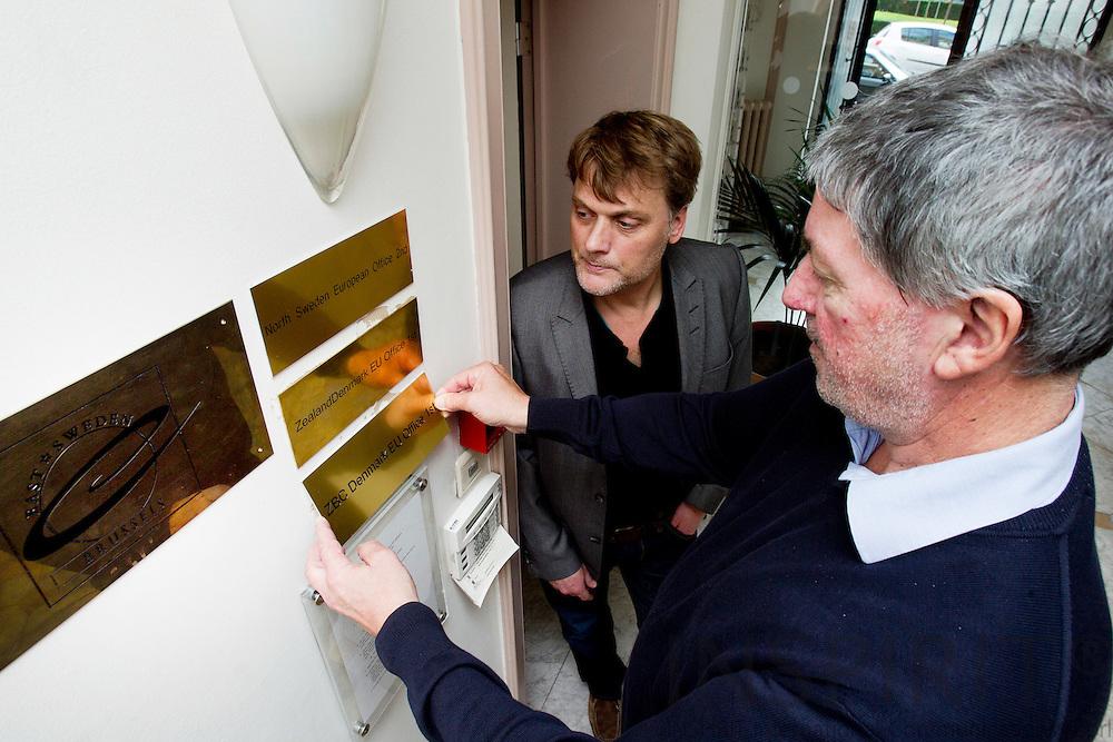 BRUSSELS - BELGIUM - 05 OCTOBER 2010 -  Steen Bengtson, konsulent og leder af Zealand Business College (ZBC) kontoret i Bruxelles, sætter skilte op mens vicedirektør Jan Bagge fra ZBC ser på.  PHOTO: ERIK LUNTANG / INSPIRIT Photo