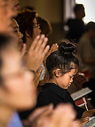 25 MARCH 2016 - BANGKOK, THAILAND: A girl prays in mass during Good Friday observances at Santa Cruz Church in Bangkok. Santa Cruz was one of the first Catholic churches established in Bangkok. It was built in the late 1700s by Portuguese soldiers allied with King Taksin the Great in his battles against the Burmese who invaded Thailand (then Siam). There are about 300,000 Catholics in Thailand, in 10 dioceses with 436 parishes. Good Friday marks the day Jesus Christ was crucified by the Romans and is one of the most important days in Catholicism and Christianity.      PHOTO BY JACK KURTZ