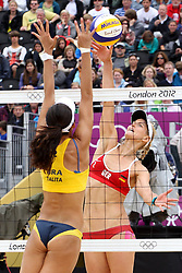 Talita Rocha of Brazil looks to block as Sara Goller of Germany returns the ball during the Women's Beach Volleyball Preliminary Phase Pool E match between Brazil and Germany held at the Horse Guards Parade stadium in London as part of the London 2012 Olympics on the 31st July 2012.Photo by Ron Gaunt/SPORTZPICS