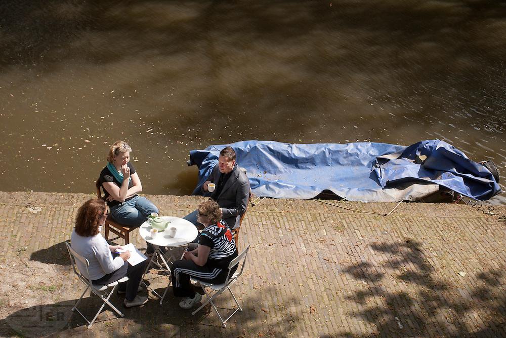 Mensen genieten aan de werf van de Oudegracht in Utrecht van een kop thee.<br /> <br /> People are drinking a cup of tea at the canals in Utrecht.