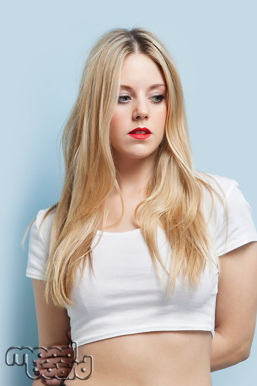 Beautiful blond woman with red lips looking down against light blue background