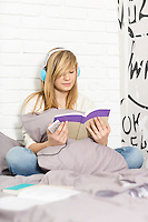 Full-length of teenage girl listening to music while reading book in bedroom
