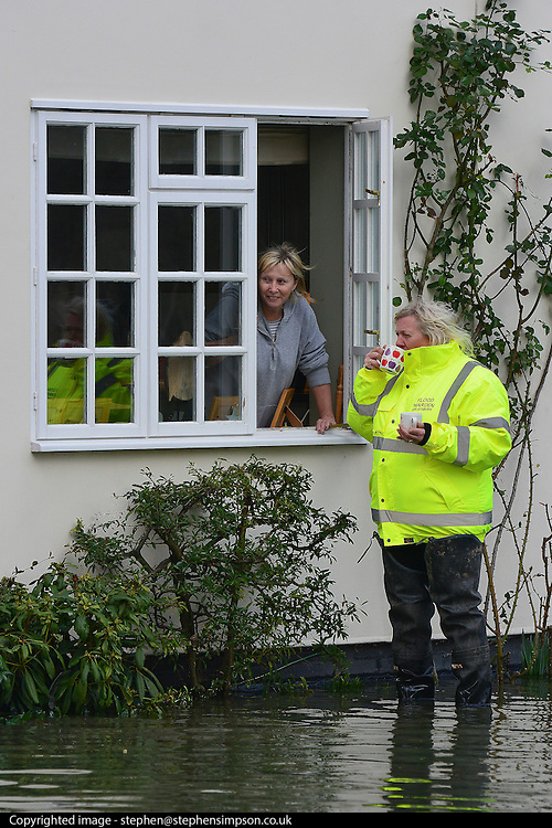 © Licensed to London News Pictures. 09/02/2014. Wraysbury, UK. A flood warden talks to a resident through a property window.  Flooding in Wraysbury in Berkshire today 9th February 2014 after the River Thames burst its banks. Photo credit : Stephen Simpson/LNP