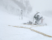 Partially obscured by a blzzard of natural and manmade snow a Nubs Nob emplyee waves his arms to co-workers who are controlling the water flow to a 60 inch fan gun that the Harbor Springs ski area uses to make snow.   Both Nubs Nob and neighboring Boyne Highlands will be open for skiing this weekend.