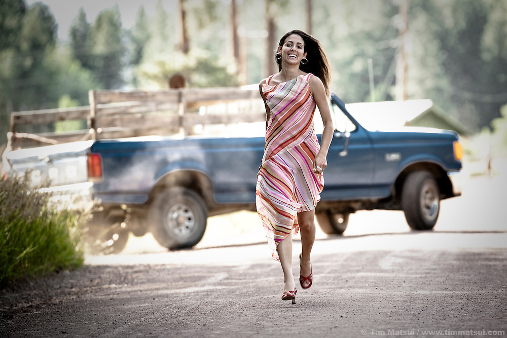 A smiling latina woman runs in a dress and heels on a dirt road.