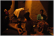 Bea Ahbeck/Fremont Argus 10/25/05<br /> <br /> Edith Nairuba, 28, HIV-positive, sits with her children and other neighborhood children as she cooks dinner for her family in Kamuli, Uganda, Oct. 25, 2005. She is the primary caretaker of her sister Florence Mukyala, 40, who is sick in tuberculosis, a complication of AIDS, and lives in a 2-room home with her and her own husband and 5 children, 4 of which are healthy.