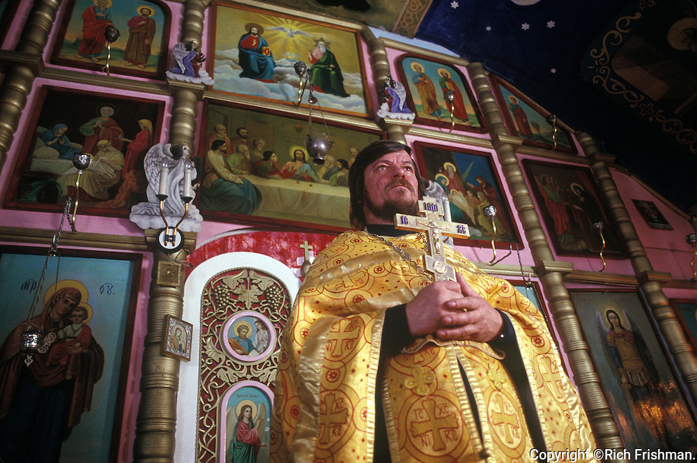 Photograph of Russian Orthodox priest in golden robes saying mass, surrounded by congregation in a tiny Russian Orthodox church with an impressive mural on ceiling in Russian Far East City of Sovetskaya Gavan.©Rich Frishman.