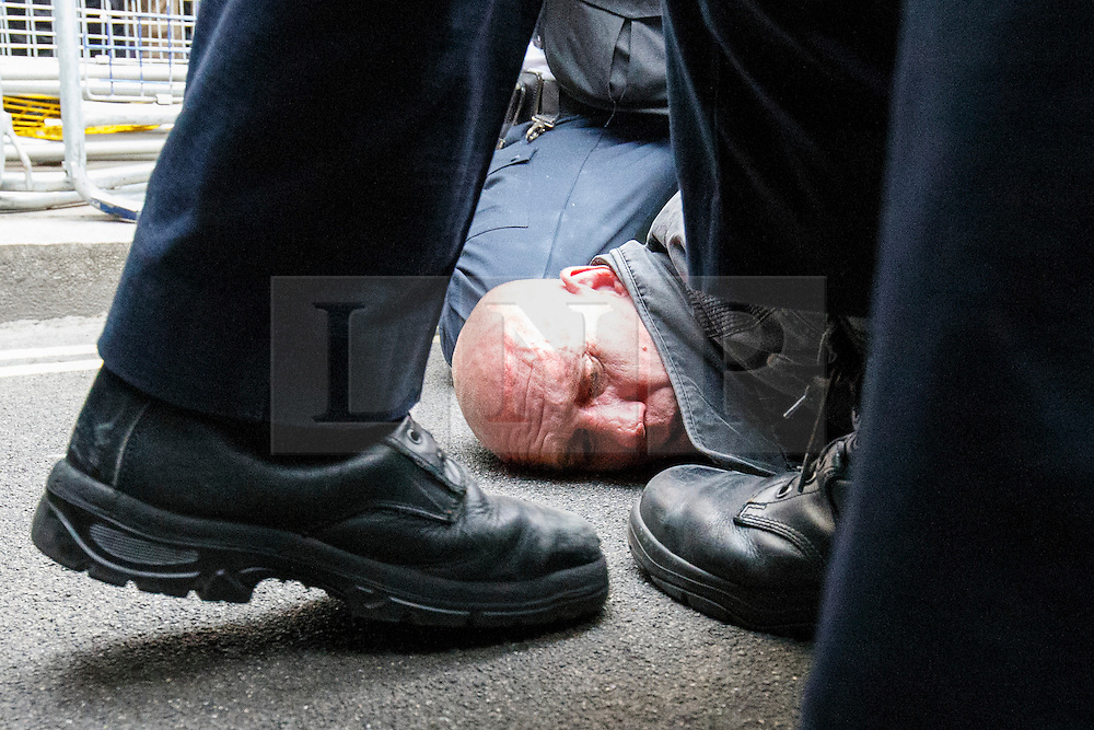 © Licensed to London News Pictures. 27/05/2015. Westminster, UK. A demonstrators being arrested whilst taking part in an End Austerity Now protest, which starts outside Downing Street in London.  Activists are demonstrating against the current conservative government and planned spending cuts. At a previous demonstration by the same group  a war memorial on Whitehall was defaced. Photo credit: Tolga Akmen/LNP