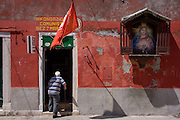 A elderly man using a walking stick enters the shadows of Italian communist party office with a street Jesus shrine on its wall, near the Arsenale in the Castello, a district of Venice, Italy.
