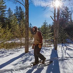 A man snowshoes next to the Hudson River near its source in New York's Adirondack Mountains. Upper Works Trail, Tahawus Tract, Newcomb, New York.